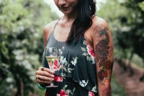 tatoo woman in vineyard with glass of champagne