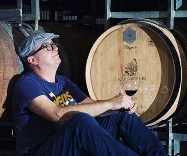 viticulteur buvant du vin devant des tonneaux