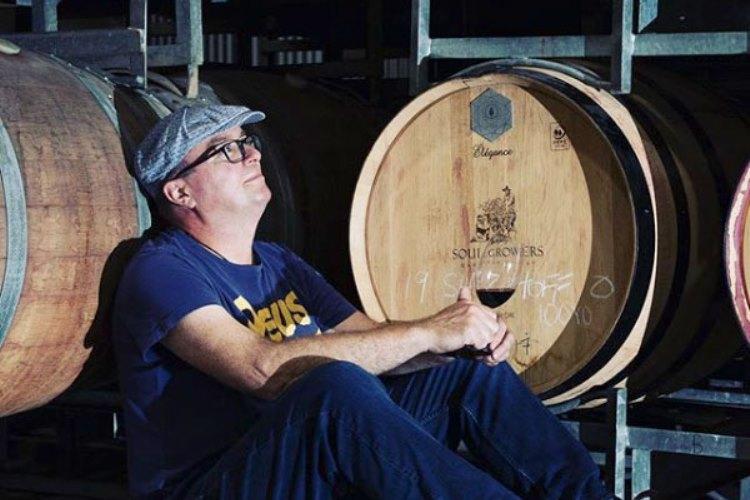 grower drinking wine in front barrels
