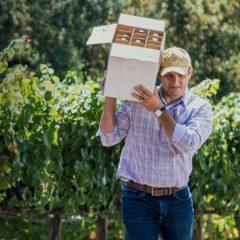 vigneron portant un carton de vins